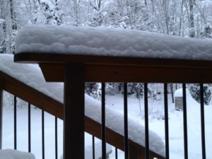 Wooden railings with black metal balusters capped with snow.